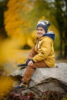 Lindo garotinho no dia de outono. criança pré-escolar em roupas outonais coloridas