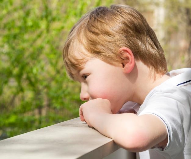 Lindo garotinho olhando do lado de fora