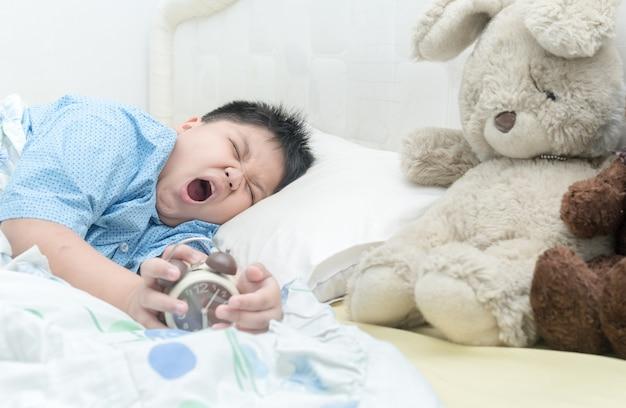 Lindo garoto acorda e bocejando.