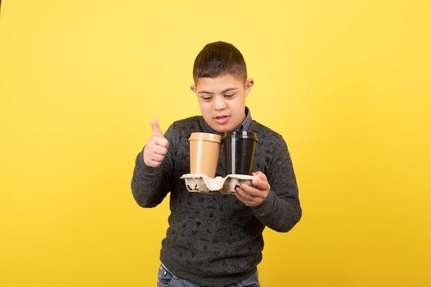 Lindo garoto com síndrome de down com xícaras de café em pé.