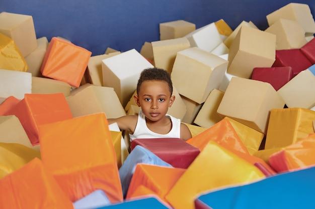 Lindo garoto negro afro-americano com camiseta branca se divertindo em uma piscina cheia de cubos coloridos e macios