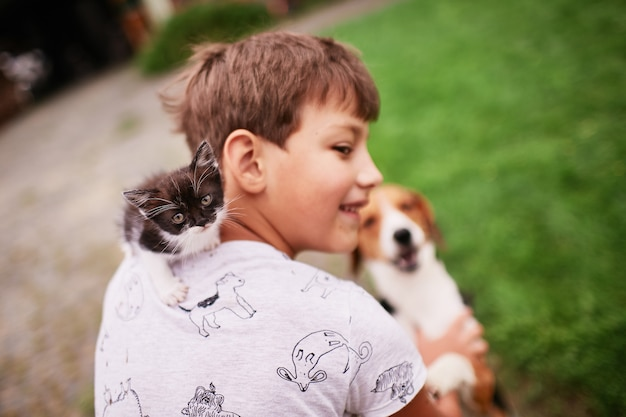 Lindo gatinho senta-se no ombro do menino