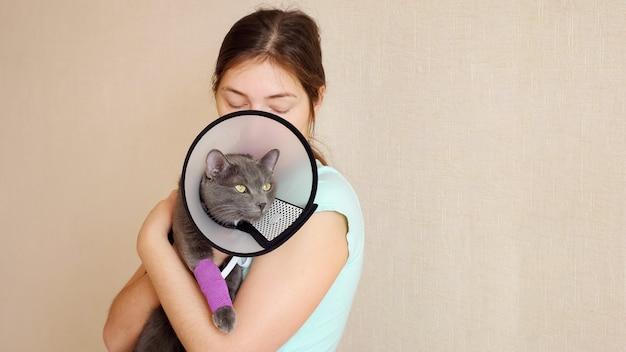 Lindo gato cinza em uma coleira veterinária com uma pata enfaixada nos braços de uma mulher.