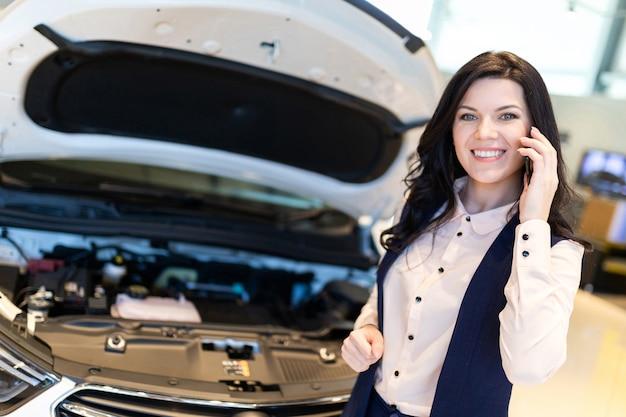 Lindo gerente de vendas inspeciona carro novo e fala por telefone no showroom da concessionária