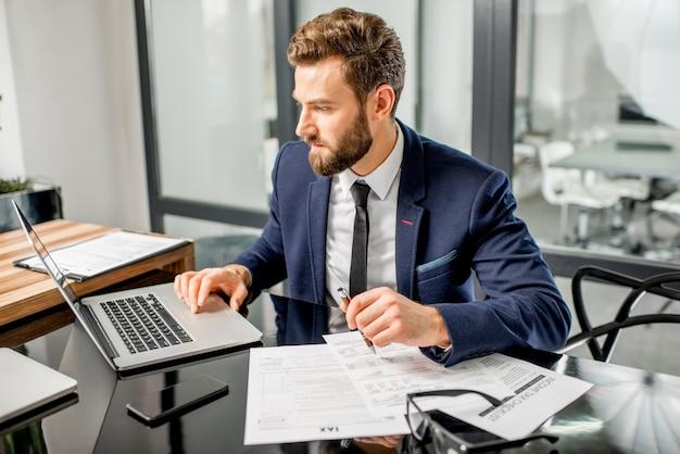 Lindo gerente fiscal vestido de terno, trabalhando com documentos e laptop no interior do escritório moderno