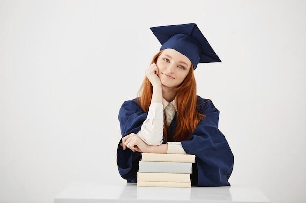 Lindo graduado feminino sentado com livros sorrindo.