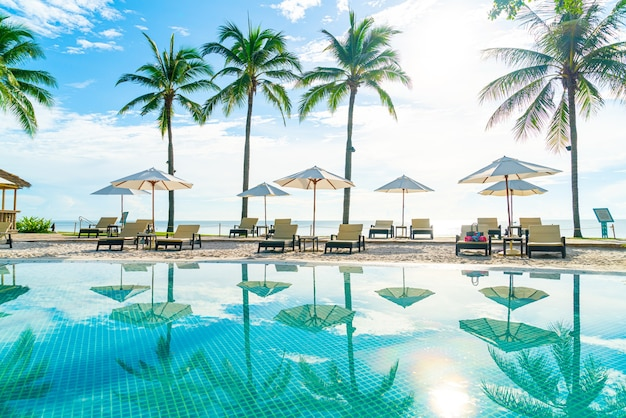 Lindo guarda-chuva e cadeira ao redor da piscina no hotel e resort - conceito de férias