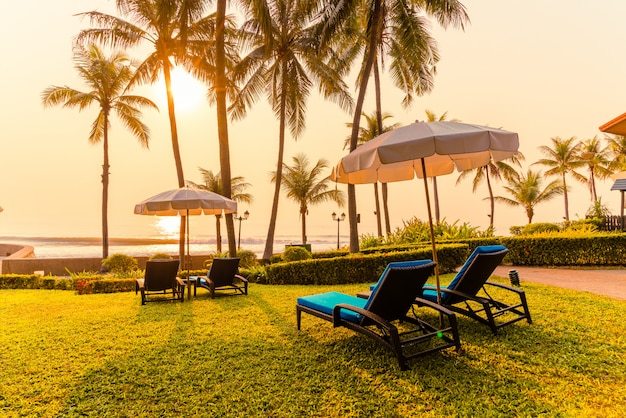Lindo guarda-chuva e cadeira ao redor da piscina no hotel e resort, férias e concerto de férias