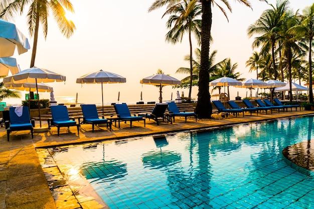 Lindo guarda-chuva e cadeira ao redor da piscina no hotel e resort - show de férias e feriado