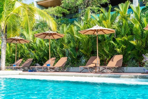 Lindo guarda-chuva e cadeira em torno da piscina no hotel e resort - conceito de férias