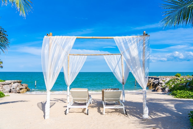 Lindo guarda-chuva e cadeira em torno do oceano do mar praia com céu azul para viajar