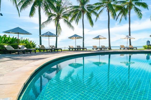 Lindo guarda-sol e cadeira ao redor da piscina no hotel e resort