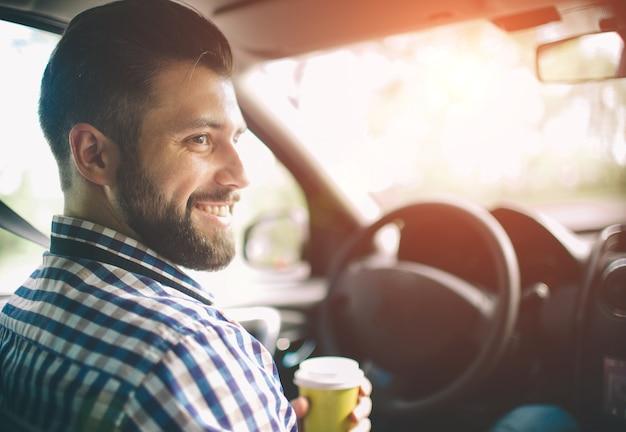 Lindo homem barbudo sorrindo enquanto está sentado nos bancos da frente do carro e ela está tomando café em um copo descartável