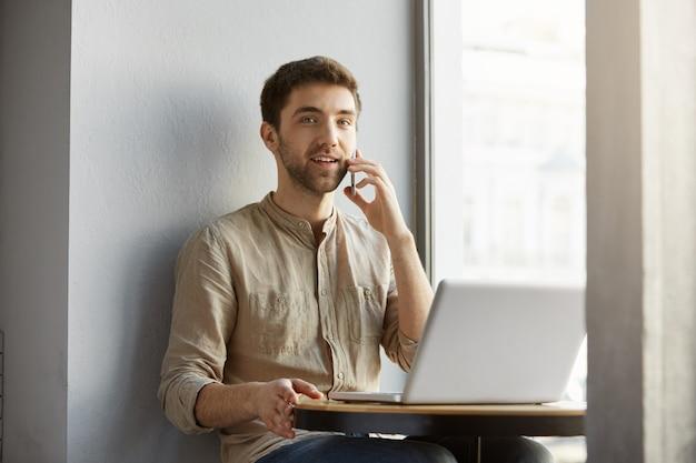 Lindo homem caucasiano com sorrisos de cabelos escuros, sentado na cafeteria com laptop, falando no telefone e. estilo de vida, conceito do negócio.