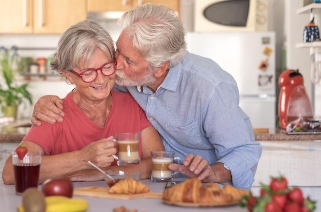 Lindo homem sênior beijando sua esposa tomando café da manhã em casa. aposentados felizes bebendo cappuccino comendo frutas e croissant