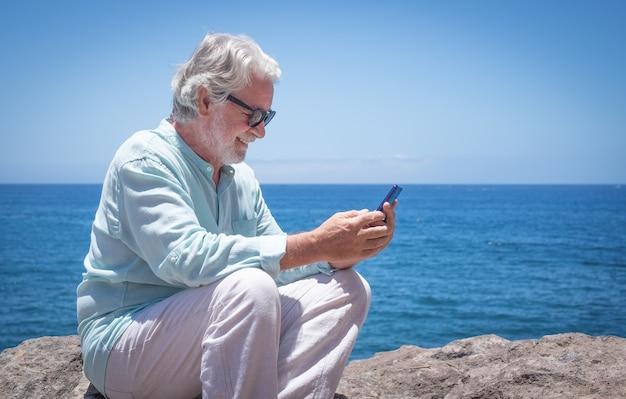 Lindo homem sênior sentado ao ar livre, no mar, enquanto usa o telefone celular, aproveitando a luz do sol