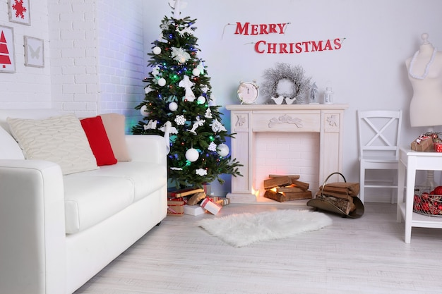 Lindo interior de natal com sofá, lareira decorativa e pinheiro
