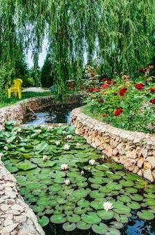 Lindo jardim paisagístico, lago com nenúfares, rosas