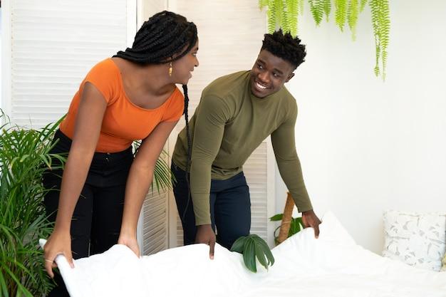 Lindo jovem casal africano fazendo cama no quarto