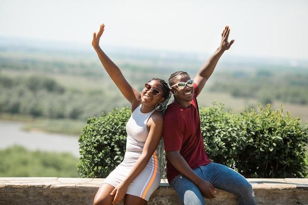 Lindo jovem casal africano homem e mulher com óculos de sol, passeando no parque