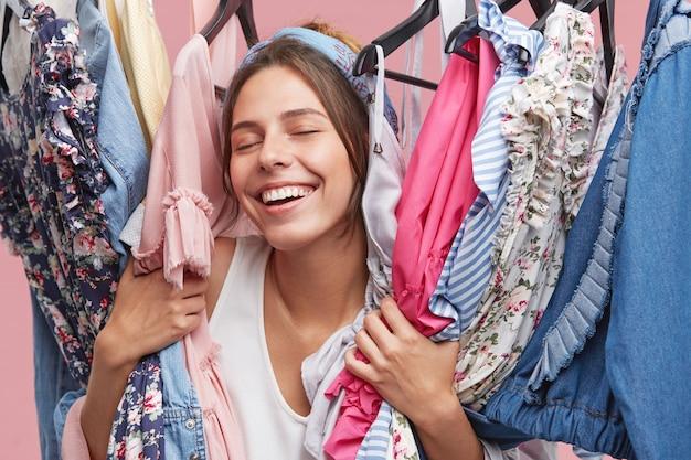 Lindo jovem europeu feminino shoppaholic fechando os olhos de prazer e diversão, mantendo diferentes roupas luxuosas e elegantes em seu guarda-roupa depois de boas compras no shopping da cidade com os amigos