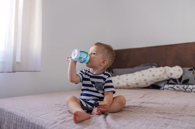 Lindo jovem loiro com sede, sentado na cama no quarto e bebendo água de sua garrafa.