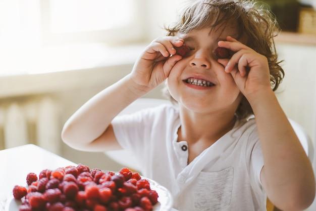Lindo lindo garotinho comendo framboesas frescas. alimentação saudável, infância e desenvolvimento.