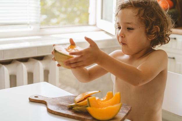 Lindo lindo garotinho comendo melão fresco.
