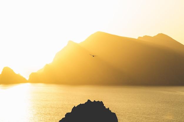 Lindo mar com montanhas ao fundo, sob um céu ensolarado