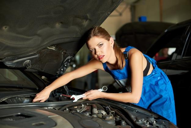 Lindo mecânico feminino repara o carro com uma chave inglesa.