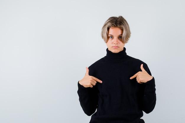 Lindo menino adolescente apontando para si mesmo em uma camisola de gola alta preta e olhando perplexo, vista frontal.