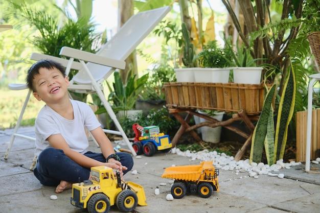 Lindo menino asiático brincando com seixos e máquinas de construção de brinquedo, criança feliz e sorridente brincando sozinha