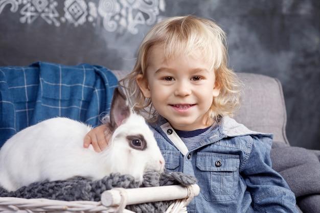 Lindo menino brinca com um coelho branco. o menino sorrindo e olhando para a câmera