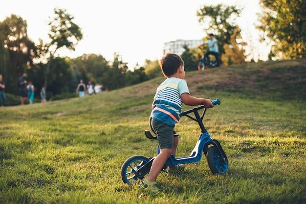 Lindo menino caucasiano andando de bicicleta no parque, brincando na grama verde e olhando para as outras crianças