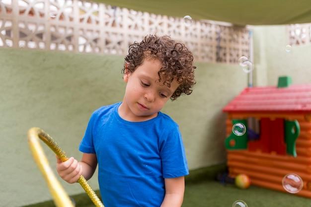 Lindo menino caucasiano de 4 a 5 anos com cabelo encaracolado no quintal brincando com bolhas de sabão