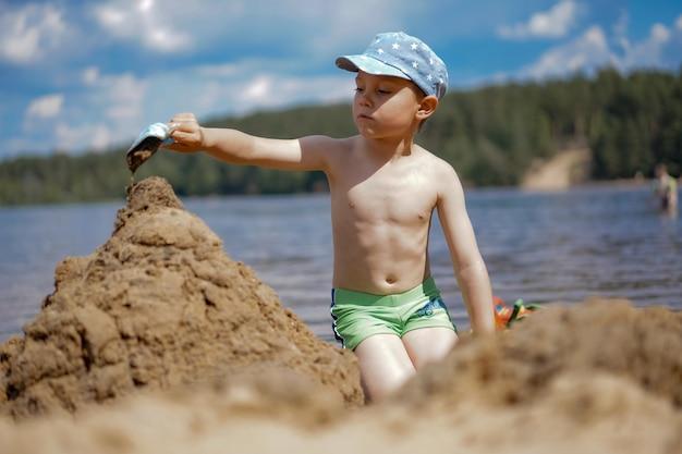 Lindo menino caucasiano fazendo castelo de areia na praia do lago da floresta, derramando água da pá para