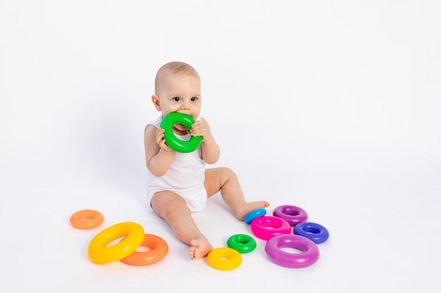 Lindo menino de 8 meses brincando com uma pirâmide em brinquedos brancos lambendo