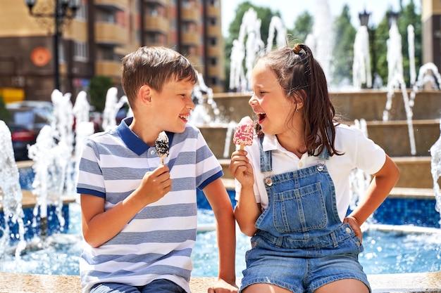 Lindo menino e menina tomando sorvete no verão