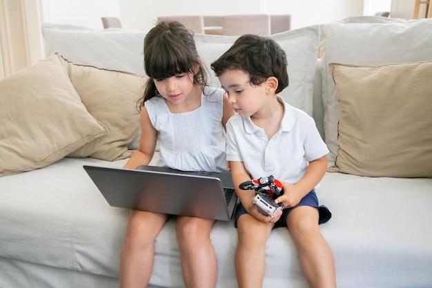 Lindo menino e uma menina sentada no sofá em casa e usando o laptop, assistindo a um vídeo ou filme.