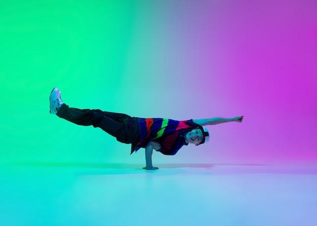 Lindo menino esportivo dançando hip-hop em roupas elegantes na parede gradiente colorida no salão de dança em luz de néon. cultura jovem, movimento, estilo e moda, ação. retrato elegante e brilhante.