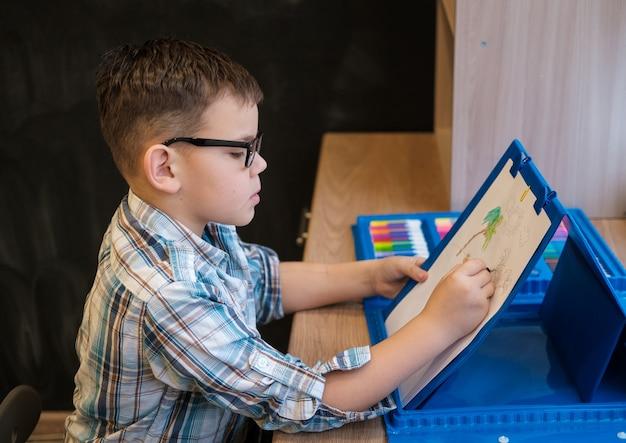 Lindo menino europeu com óculos desenha no papel com lápis, sentado à mesa. o processo de criação de um desenho infantil