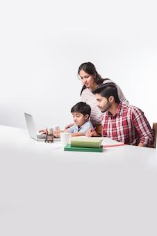 Lindo menino indiano com pai e mãe estudando ou fazendo lição de casa em casa usando laptop e livros - conceito de escolaridade online