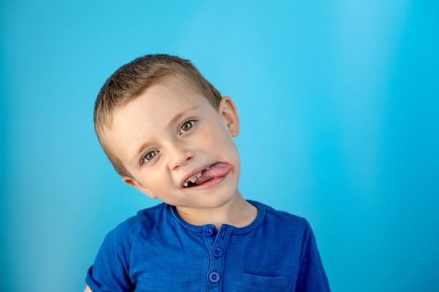 Lindo menino mostra a língua e se diverte na parede azul.