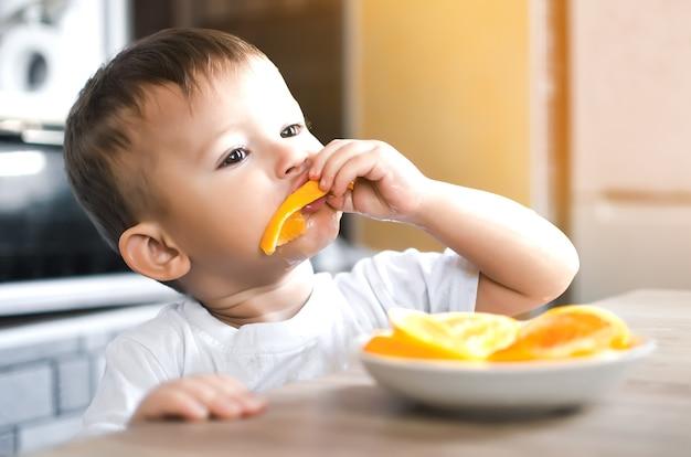 Lindo menino na cozinha comendo uma laranja avidamente cortada em fatias