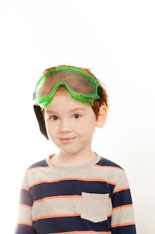 Lindo menino ruivo usando óculos de proteção de construção, em uma parede de luz