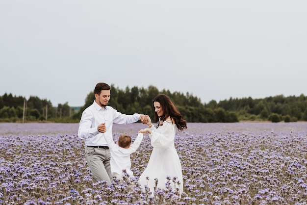 Lindo menino sorridente com a mãe e o pai se divertindo em um campo florido.
