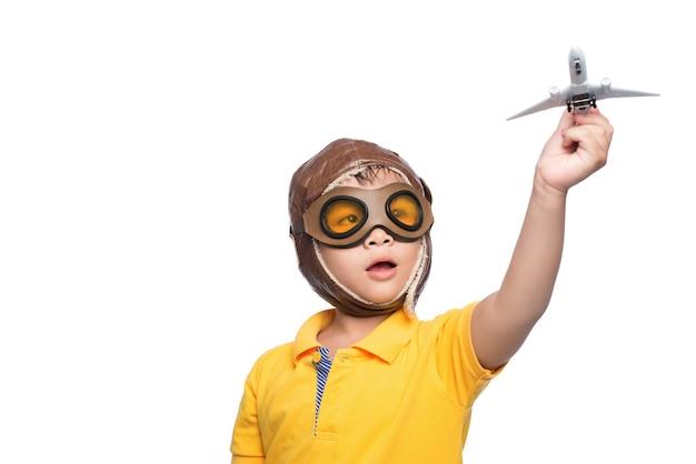 Lindo menino sorridente criança no capacete em um fundo branco, brincando com um avião.