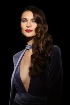 Lindo modelo com pele limpa e saudável e vestido de veludo posando no quarto escuro