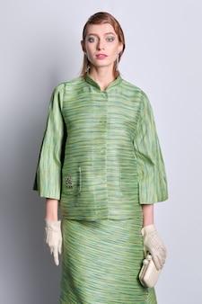 Lindo modelo de jaqueta de seda verde e saia com penteado à moda antiga