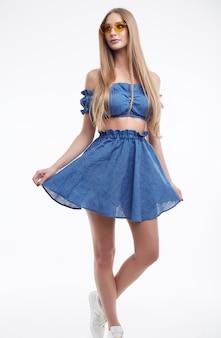 Lindo modelo feminino com cabelos longos, posando em vestido azul da moda